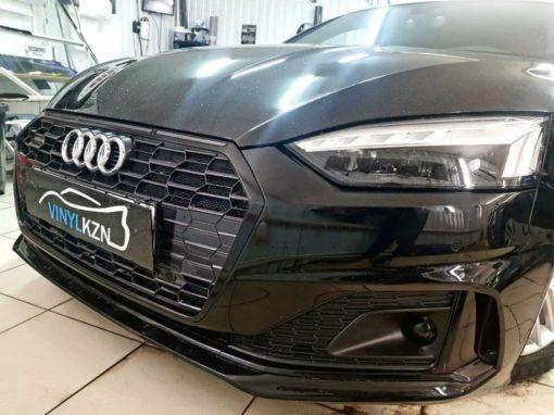 Оклейка черной глянцевой пленкой окантовки решетки и нижних молдингов на переднем и заднем бампере — Audi A5